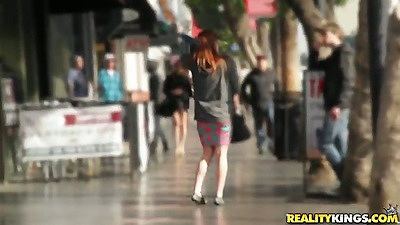 Outdoors in the public a girl with an attached vibrator